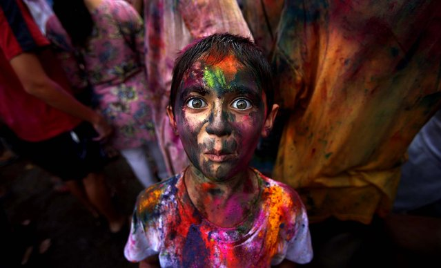 A boy, his face smeared with colored powder, reacts as he poses for a photo during a celebration of the Hindu festival Holi in Kuala Lumpur, Malaysia, on March 31, 2013. (Photo by Seng Sin/Associated Press)