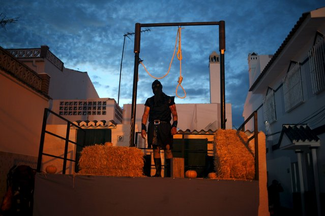 """A man dressed as an executioner takes part in the second edition of """"Noche del Terror"""" (Horror night) during Halloween celebrations in the neighborhood of Churriana, near Malaga, southern Spain, October 31, 2015. (Photo by Jon Nazca/Reuters)"""