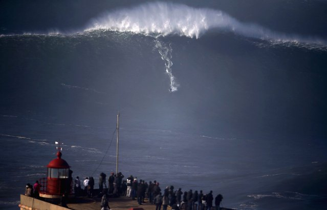 A surfer drops in on a large wave at Praia do Norte, in Nazare December 11, 2014. Praia do Norte beach has gained popularity with big wave surfers since Hawaiian surfer Garrett McNamara broke a world record for the largest wave surfed here in 2011. (Photo by Rafael Marchante/Reuters)