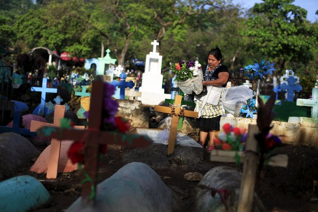 A woman places flowers on the grave of a relative during celebration of the Day of the Dead in Nahuizalco, El Salvador November 2, 2015. (Photo by Jose Cabezas/Reuters)