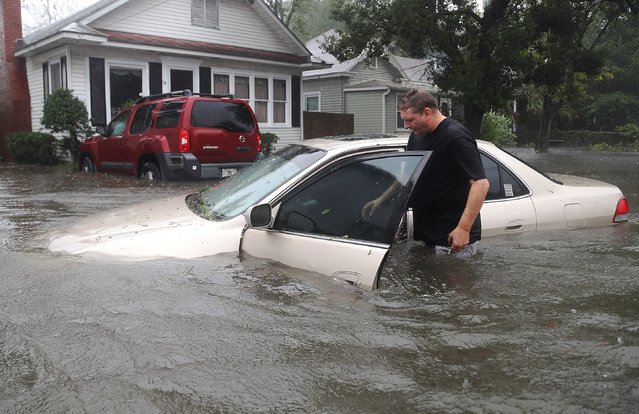 Rob Birch checks on his car which floated out of his drive way as Hurricane Matthew passes through the area on October 7, 2016 in St Augustine, Florida. Florida, Georgia, South Carolina and North Carolina all declared a state of emergency in anticipation of Hurricane Matthew. (Photo by Joe Raedle/Getty Images)