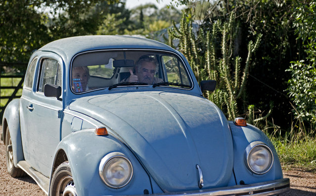 In this May 2, 2014 file photo, Uruguay's President Jose Mujica flashes a thumbs up as he and and his wife, Sen. Lucia Topolansky, ride away from their home after giving an interview, on the outskirts of Montevideo, Uruguay. (Photo by Matilde Campodonico/AP Photo)