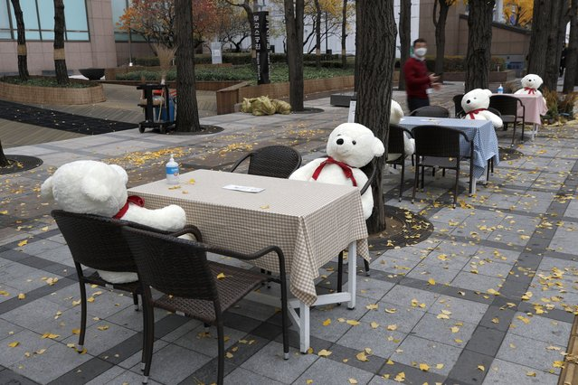 Tables and chairs are placed with hand sanitizers and stuffed toys while maintaining social distancing in downtown Seoul, South Korea, Wednesday, November 18, 2020. This is one of the programs for a week, for the people who are tired from COVID-19, can enjoy while maintaining social distancing and for downtown revitalization. (Photo by Lee Jin-man/AP Photo)