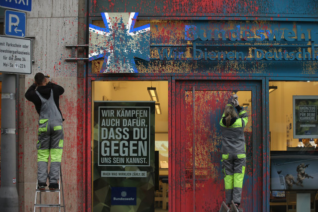 """Workers scrape away paint splattered by vandals on the facade of a recruiting center of the German armed forces, the Bundeswehr, next to a sign in the window that reads: """"We also fight for you to be able to be against us"""" on November 9, 2015 in Berlin, Germany. The Bundeswehr will celebrate its 60th anniversary on Wednesday. (Photo by Sean Gallup/Getty Images)"""