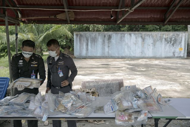 Policemen hold bags with personal possessions of 2004 tsunami victims before they are photographed outside a police station in Takua Pa, in Phang Nga province December 19, 2014. (Photo by Damir Sagolj/Reuters)
