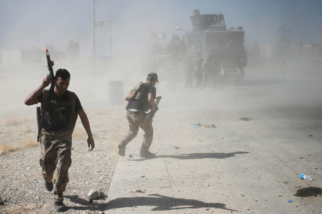 Iraqi special forces soldiers run for cover during clashes with Islamic States fighters in Bartella, east of Mosul, Iraq October 20, 2016. (Photo by Goran Tomasevic/Reuters)
