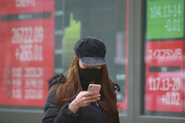 A woman wearing a face mask to help curb the spread of the coronavirus walks by an electronic stock board of a securities firm in Tokyo, Wednesday, December 9, 2020. Asian shares logged strong gains on Wednesday after another round of record highs for major indexes on Wall Street. (Photo by Koji Sasahara/AP Photo)