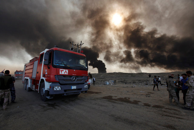 Fire trucks are seen in Qayyara, Iraq, October 22, 2016. The fumes in the background are from oil wells that were set ablaze by Islamic State militants. (Photo by Alaa Al-Marjani/Reuters)