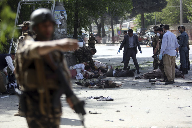 Victims lie on the ground after the explosions in Kabul, Afghanistan, Monday, April 30, 2018. (Photo by Rahmat Gul/AP Photo)
