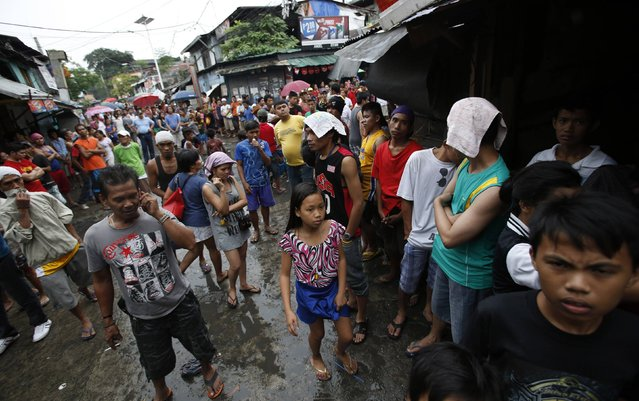 Residents whose houses were gutted by a fire gather on a road at a slum colony in Quezon city, Metro Manila January 1, 2015. (Photo by Erik De Castro/Reuters)