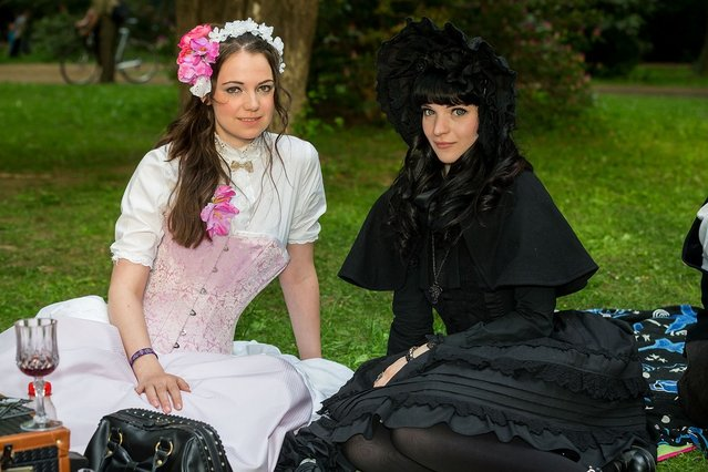 Two girls in black and white Victorian clothing pose for pictures during the traditional park picnic on the first day of the annual Wave-Gotik Treffen, or Wave and Goth Festival, on May 17, 2013 in Leipzig, Germany. The four-day festival, in which elaborate fashion is a must, brings together over 20,000 Wave, Goth and steam punk enthusiasts from all over the world for concerts, readings, films, a Middle Ages market and workshops. (Photo by Marco Prosch)