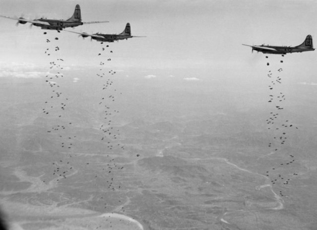 Bomber Command planes of the U.S. Far East Air Forces rain tons of high demolition bombs on a strategic military target of the Chinese Communists in North Korea on January 18, 1951. As part of the stepped-up aerial offensive against the enemy, attacks such as this one are staggering the Chinese, thus helping UN ground forces to stem the Communist push down the center of the Korean peninsula. The planes above blasting the Chinese  hordes are B-29 Superfortress medium bombers. (Photo by AP Photo)