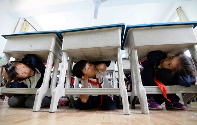 Primary school students take part in an earthquake drill ahead of the 10th anniversary of the 2008 Sichuan earthquake, inside a classroom in Handan, Hebei province, China May 11, 2018. (Photo by Reuters/China Stringer Network)