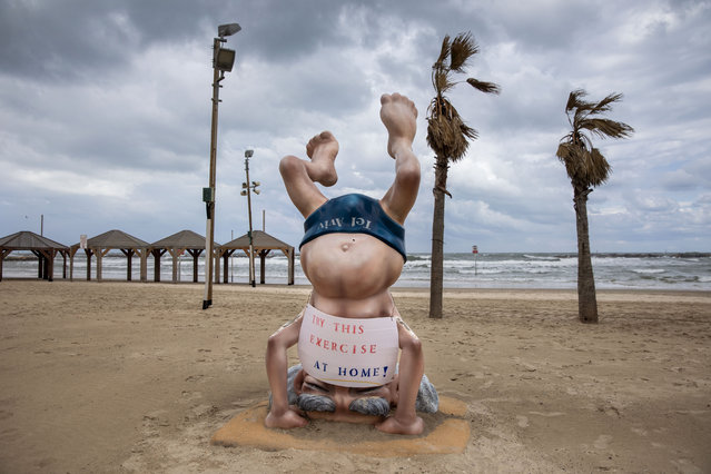 A sign calling people to stay home to reduce the spread of the new coronavirus is placed on a statue of the first Israeli Prime Minister David Ben Gurion at a beach in Tel Aviv, Israel, Friday, March 20, 2020. Prime Minister Benjamin Netanyahu said he was further tightening restrictions on movement, with exceptions only to go out for food or other urgent matters. (Photo by Oded Balilty/AP Photo)