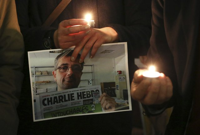 People hold candles as they pay tribute to the victims of a shooting by gunmen at the offices of weekly satirical magazine Charlie Hebdo in Paris, in front of the European Parliament in Brussels January 7, 2015. (Photo by Francois Lenoir/Reuters)