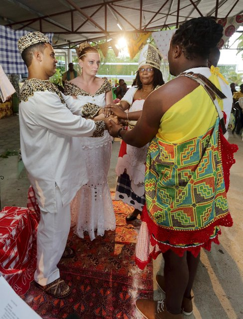 Dutch migrants Reggio de Jong (L) and Elisabeth Cobben (2nd L) hold hands as they are wedded by priest Dorenia Babel (C) in the second public marriage ever held under the African-American Winti religion in district Para, Suriname, November 18, 2015. (Photo by Ranu Abhelakh/Reuters)