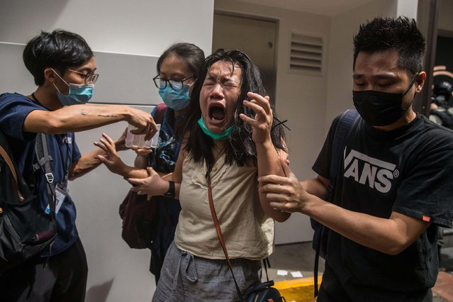 A woman reacts after she was hit with pepper spray deployed by police as they cleared a street with protesters rallying against a new national security law in Hong Kong on July 1, 2020, on the 23rd anniversary of the city's handover from Britain to China. A man found in possession of a Hong Kong independence flag became the first person to be arrested under Beijing's new national security law for the city, police said on July 1. (Photo by Dale De La Rey/AFP Photo)