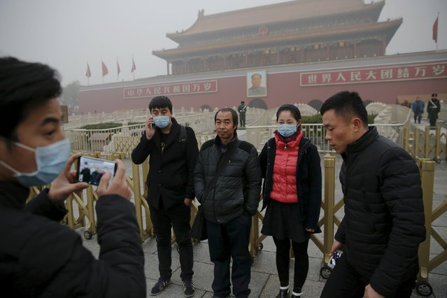 People wearing protective masks have their picture taken near the Tiananmen Gate on an extremely polluted day as hazardous, choking smog continues to blanket Beijing, China December 1, 2015. (Photo by Damir Sagolj/Reuters)