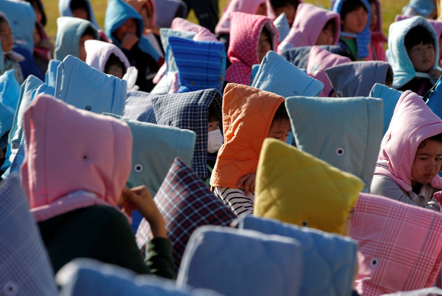 School children wearing padded hoods to protect them from falling debris gather in an evacuation shelter on a hill during a tsunami simulation drill ahead of World Tsunami Awareness Day at Futaba elementary school in Choshi, Chiba Prefecture, Japan, November 4, 2016. (Photo by Kim Kyung-Hoon/Reuters)