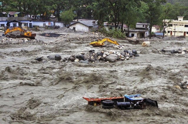 Bulldozer and other vehicles are drifted in a flooded river in Uttarkashi district, India, Monday, June 17, 2013. Torrential rain and floods washed away buildings and roads, killing at least 23 people on Monday in the northern Indian state of Uttarakhand, officials said Monday. (AP Photo)