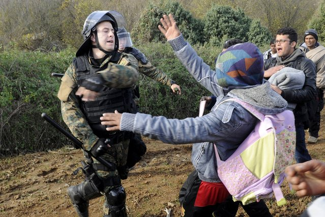 A Macedonian police officer hits a stranded migrant attempting to cross the Greek-Macedonian border, near Gevgelija, Macedonia December 2, 2015. Picture taken from the Greek side of the border. (Photo by Alexandros Avramidis/Reuters)