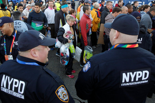 NYPD officers watch as runners arrive to compete for the 2016 New York City Marathon in the Manhattan borough of New York City, U.S., November 6, 2016. (Photo by Brendan McDermid/Reuters)
