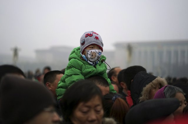 """A boy wearing a mask sits on the shoulders of a man as they watch a flag-raising ceremony amid heavy smog at the Tiananmen Square, after the city issued its first ever """"red alert"""" for air pollution, in Beijing, China, December 8, 2015. (Photo by Reuters/Stringer)"""