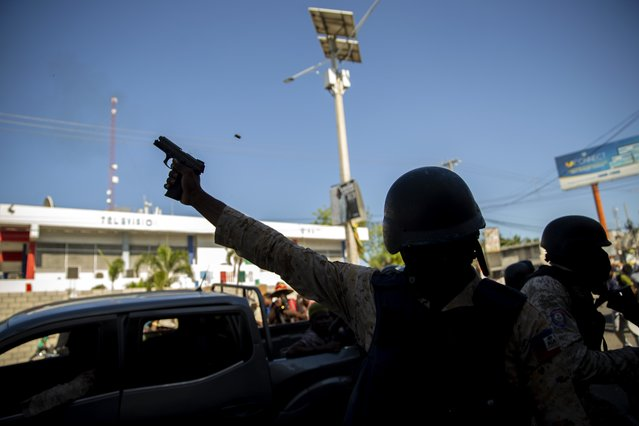 A police officer fires his weapon to disperse demonstrators during a protest to demand the resignation of Haitian President Jovenel Moise in Port-au-Prince, Haiti, Sunday, February 7, 2021. (Photo by Dieu Nalio Chery/AP Photo)