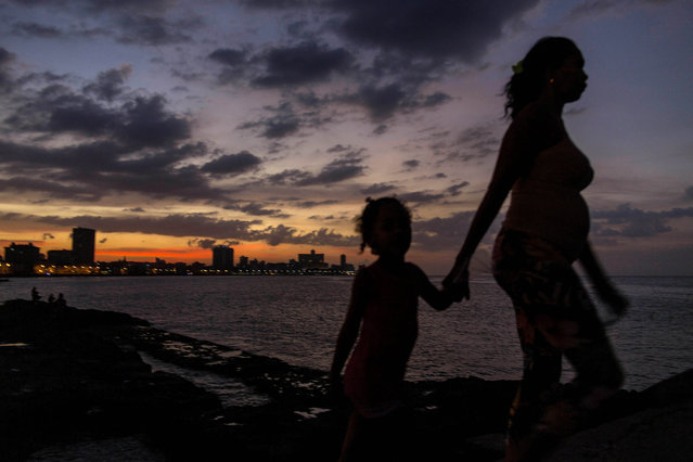 In this January 3, 2015, file photo, a woman leads a girl by the hand to the Malecon as the sun sets in Havana, Cuba. Everyone warns you Old Havana is a facade, but it's impossible not to be taken by its charms. For a foreigner who isn't coming with predetermined notions of Cuba as global boogeyman or socialist paradise, each alley and avenue, each conversation with a Cuban, complicates the picture. (Photo by Ramon Espinosa/AP Photo)