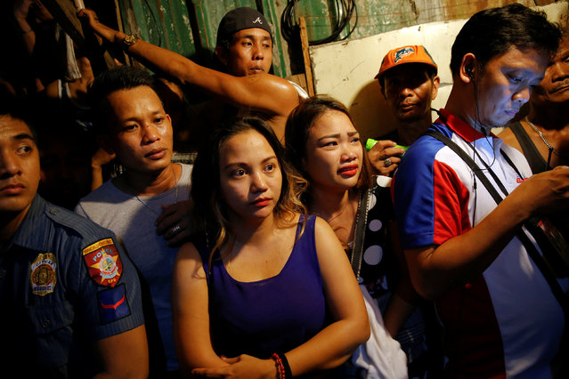 Relatives and onlookers wait for investigation to be done outside a house in which five people were killed in Manila, Philippines early November 1, 2016. (Photo by Damir Sagolj/Reuters)