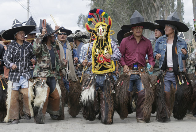 Indigenous mean in traditional costumes dance on the road to Cotacachi, Ecuador to take over the town's main plaza to celebrate the festival of the Sun, Sunday, June 24, 2018. (Photo by Dolores Ochoa/AP Photo)