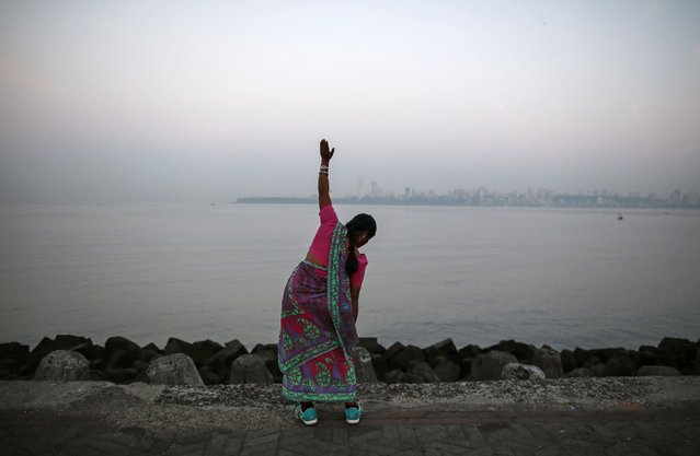 A woman wearing a saree, a traditional cloth used for women's clothing, exercises along the Arabian Sea in Mumbai January 22, 2015. (Photo by Danish Siddiqui/Reuters)