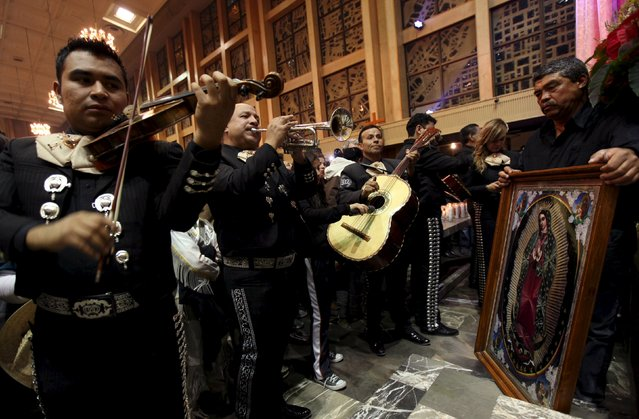 A group of Mariachis plays as a pilgrim holds an image of the Virgin of Guadalupe during an annual pilgrimage in honor of the Virgin, the patron saint of Mexican Catholics, at the Cathedral of Ciudad Juarez, Mexico December 12, 2015. (Photo by Jose Luis Gonzalez/Reuters)