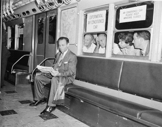 While other subway passengers perspire in the warm and humid underground station, Paul Forman appears cool and comfortable in the experimental air conditioned train which made its first run in New York City, July 9, 1956. The test run, which included six air conditioned cars and two old cars, was made on the East Side IRT line. (Photo by Harry Harris/AP Photo)