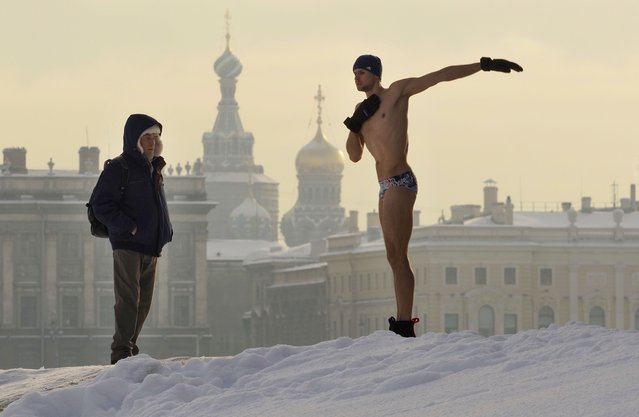 A man warms up prior to swimming in an ice hole in the Neva River St. Petersburg, Russia, Wednesday, February 10, 2021. The temperature in St. Petersburg is –15C ( 5 °F). (Photo by Dmitri Lovetsky/AP Photo)