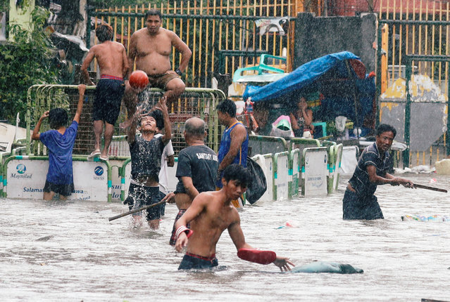 Residents frolic on a flooded street caused by monsoon rains and Tropical Storm Son-Tinh in Quezon city, Metro Manila, Philippines on July 17, 2018. (Photo by Erik De Castro/Reuters)