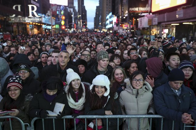 People stand in a penned of area of Times Square during New Year's Eve celebrations in Manhattan December 31, 2015. (Photo by Carlo Allegri/Reuters)