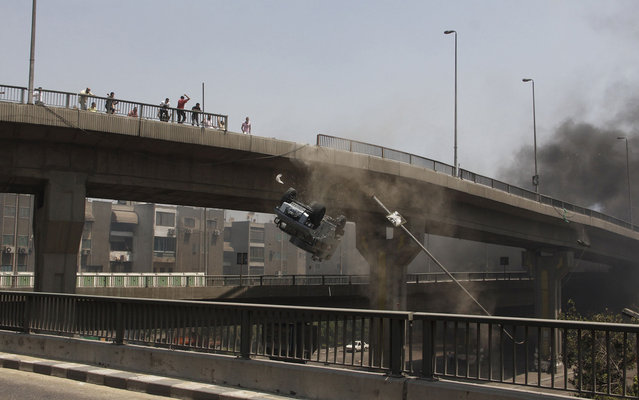 A police vehicle is pushed off of the Sixth of October Bridge in Cairo on August 14, 2013. (Photo by Sabry Khaled/AP Photo/El Shorouk Newspaper)