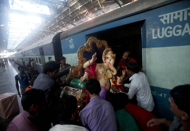 A clay idol of elephant headed Hindu god Ganesh is carried onto a passenger train before being transported to a place of worship in Mumbai, India, Sunday, September1, 2013. Ganesh Chaturthi, celebrated as the birthday of Lord Ganesha, begins September 9. The idols will be immersed in water bodies at the end of the festival. (Photo by Rafiq Maqbool/AP Photo)