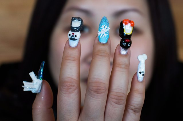 Model Helen Kwok displays the nail art completed by a competitor at the Canada Nail Cup in Vancouver, Monday, February 16, 2015. (Photo by Darryl Dyck/AP Photo/The Canadian Press)