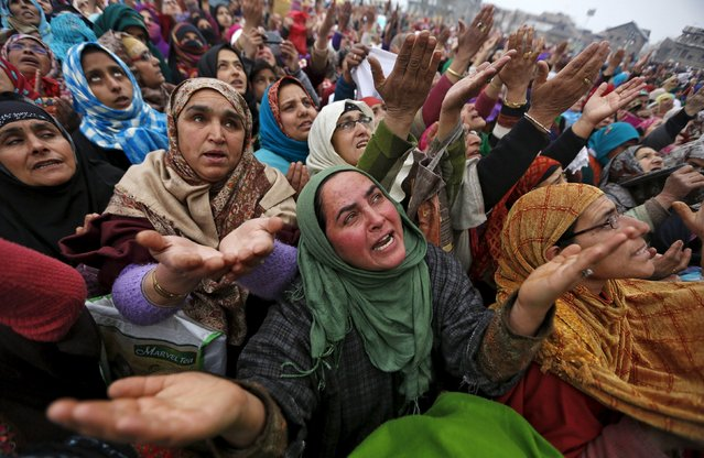 Kashmiri Muslims women react upon seeing a relic believed to be hair from the beard of Prophet Mohammed, being displayed on the Friday following the festival of Eid-e-Milad-ul-Nabi at Hazratbal shrine in Srinagar, January 1, 2016. Thousands of Kashmiri Muslims gather every year at the shrine which houses the relic on the Friday following Eid-e-Milad-ul-Nabi, the prophet's birth anniversary, which was celebrated on December 24 in Kashmir. (Photo by Danish Ismail/Reuters)