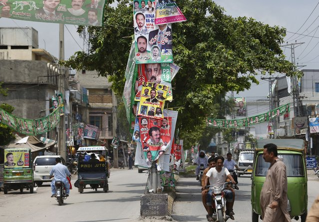 Banners of election candidates from political parties are displayed on a road in Rawalpindi, Pakistan, Tuesday, July 24, 2018. As Pakistan prepares to make history Wednesday by electing a third straight civilian government, rights activists, analysts and candidates say the campaign has been among its dirtiest ever, imperiling the country's wobbly transition to democratic rule. (Photo by Anjum Naveed/AP Photo)