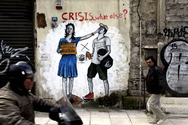 A pedestrian passes anti-austerity graffiti in Athens, Monday, February 16, 2015. Greece's radical left government and its European creditors are heading into new talks Monday on the debt-heavy country's stuttering bailout program, but expectations are low despite a fast-approaching deadline for some kind of deal. (Photo by Thanassis Stavrakis/AP Photo)