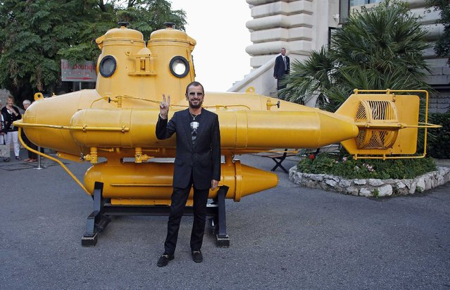 """British musician and artist Ringo Starr poses near a yellow submarine before receiving the """"Insigne de Commandeur de l'ordre des Arts et Lettres"""" medal during a ceremony as part of the art exhibition """"Arternativelight Passion/Ocean"""" at the Oceanographic Museum in Monaco September 24, 2013. (Photo by Eric Gaillard/Reuters)"""