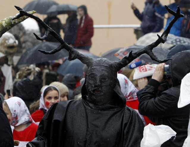 A masked reveler participates in the carnival procession through the southwestern Macedonian village of Vevcani, on Wednesday, January 13, 2016. Participants find an inspiration for their masks in the actual political events and perform various pagan rituals. In its fourteen centuries-old tradition, the Vevcani carnival is always held on St. Basil's day, marking the beginning of the New Year by the Julian calendar. (Photo by Boris Grdanoski/AP Photo)