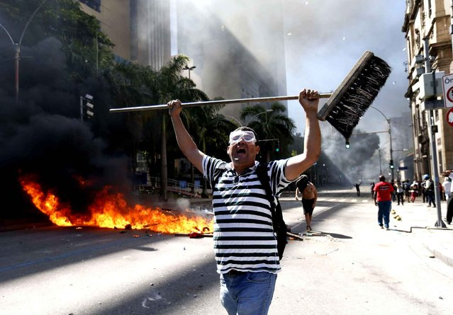 A man holds a broom as he shouts during clashes with police outside the state legislature during a protest against austerity measures being discussed in the chamber, in Rio de Janeiro, Brazil, Tuesday, December 6, 2016. Legislators were voting on measures to address the state's deepening financial crisis, in which thousands of state employees and retirees have not been paid or have been paid months late. (Photo by Silvia Izquierdo/AP Photo)