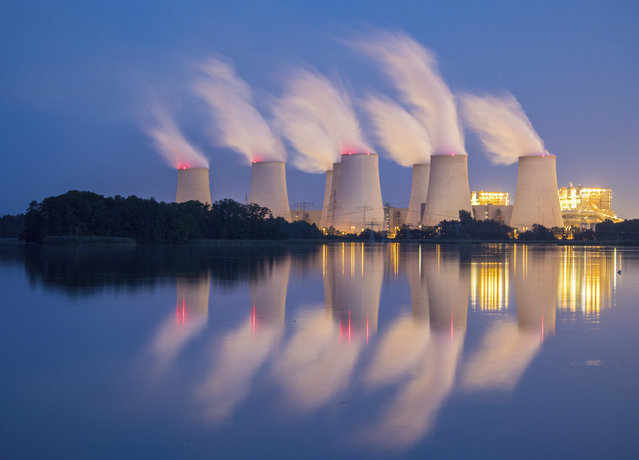 In this September 19, 2018 photo steam and cooling towers of a lignite power plant are reflected in a pond in Peitz, eastern Germany. (Photo by Patrick Pleul/DPA via AP Photo)