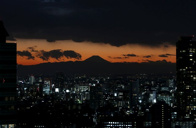 The silhouette of Japan's highest mountain Mount Fuji (C) is seen beyond buildings in Tokyo in this December 12, 2012 file photo. (Photo by Issei Kato/Reuters)