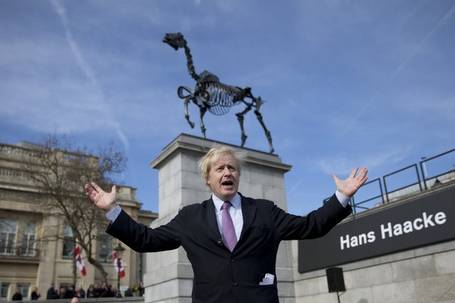 """London mayor Boris Johnson poses for photographers in front of the sculpture """"Gift Horse"""", which portrays a skeletal horse by German-born artist Hans Haacke, after it was unveiled as the new commission for the Fourth Plinth, in Trafalgar Square, London, Thursday, March 5, 2015.  The 4.6 meter high bronze sculpture has an electronic ribbon attached to its front leg displaying a live ticker of the London Stock Exchange.  (AP Photo/Matt Dunham)"""