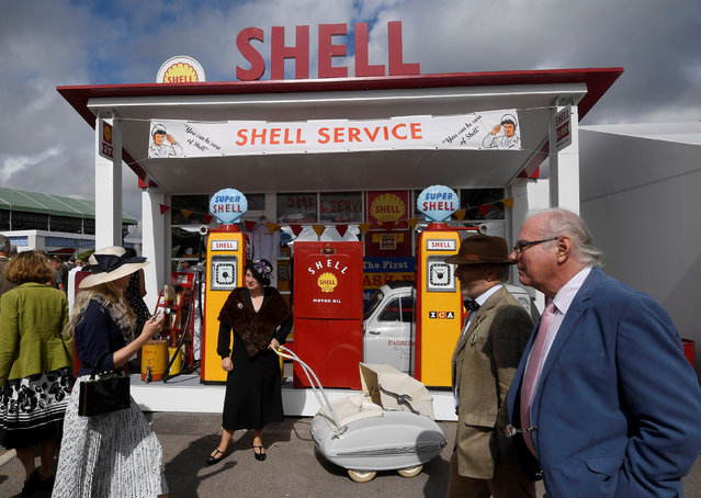 Visitors and car enthusiasts walk in front of restored Shell petrol pumps as they attend the Goodwood Revival historic motor racing festival, an annual event celebrating a mid-twentieth century heyday of the racing circuit, near Chichester, Britain, September 9, 2016. (Photo by Toby Melville/Reuters)